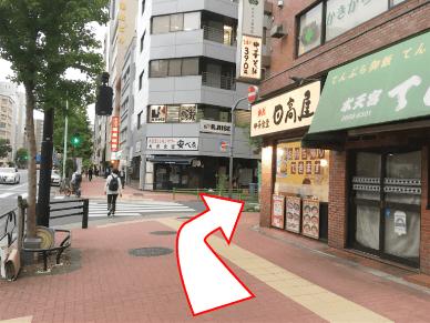 右手に日高屋がある角を右折し、110m直進。左手に青色・緑色・橙色の看板がある建物の5階。備長炭焼一久の向かい。